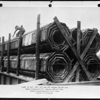 Substitute materials. A shipment of 1,488 feet of 18-inch, 24-inch, 30-inch and 36-inch wooden pipe on one flat car. Weight 70,020 pounds. An equal footage of reinforced concrete pipe weighs 455,412 pounds, requires over ten cars. These pipes, used in place of corrugated iron or reinforced concrete pipes, are made of sections cut from short lengths of wood. Locking of adjacent rings with hardwood dowel pins produces a flexible structure. About 100,000 feet of these wooden pipes were installed in 1942 in drainage culverts, storm sewers and conduits, under highways and at army camps, naval stations, airfields and ordnance plants. Albert Freeman, William Perlitch or Roger Smith, 1943. Collectie Farm Security Administration - Office of War Information Photograph Collection (Library of Congress)